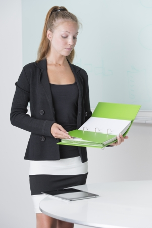 Beautiful female entrepreneur studying report in her workplace Stock Photo