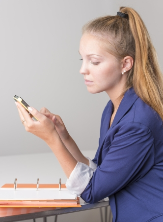 Attractive businesswoman reading message on mobile phone in her workplace photo