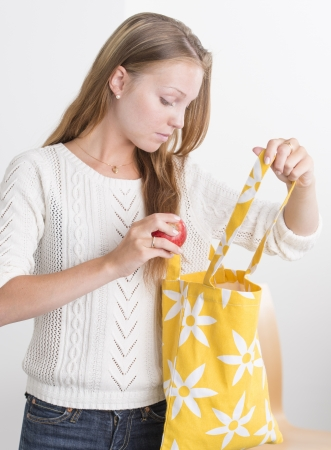 Attractive female holding ecological textile bag and apple Stock Photo
