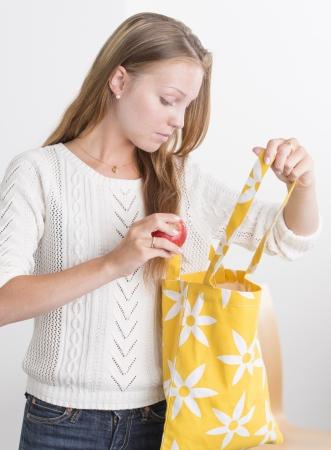reusable: Femmina attraente che tiene sacchetto ecologico tessile e mela