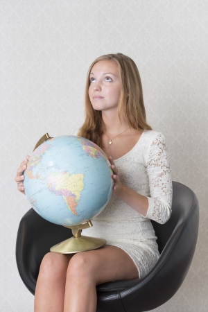 Beautiful young female holds a globe of the planet earth looking pensive photo