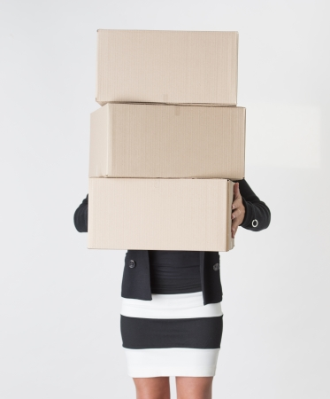 Young adult female carry a stack of boxes during a move from one office to another photo