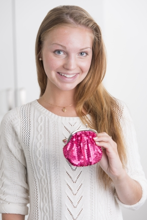 Attractive female holding pink wallet looking at camera and smiling photo