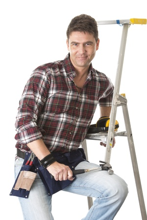 Isolated portrait of man working with construction sitting on a ladder and holding hammer Stock Photo