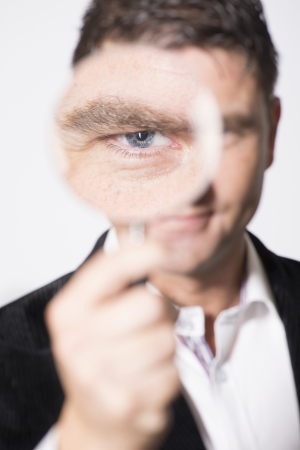 Confident businessman inspect with magnifier