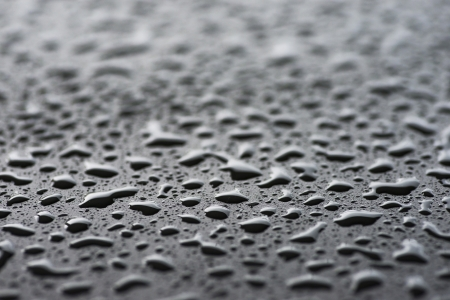 Closeup of black wet surface with droplets of water