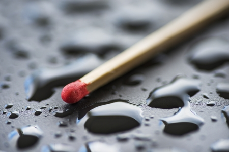 Closeup unused matchstick lying on black wet surface covered with droplets of water
