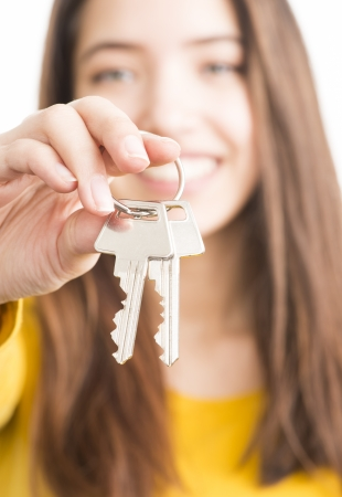 Beautiful teenage girl showing a pair of keys