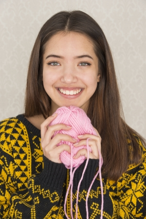 Beautiful teenage girl hold a ball of pink cotton yarn used for knitting or crochet work photo
