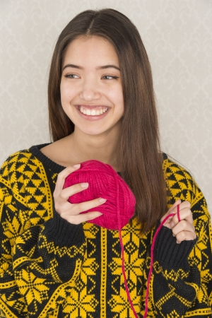 Beautiful teenage girl hold a ball of red cotton yarn used for knitting or crochet work photo