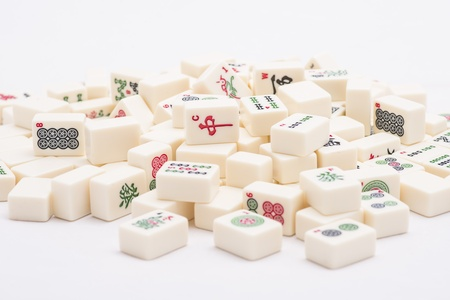 mahjong: Pile of asian Mah Jong board game pieces on white background