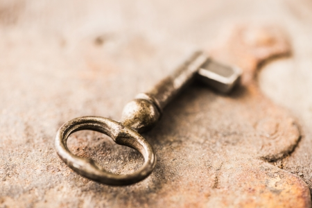 Close-up of old antique key on wooden background photo