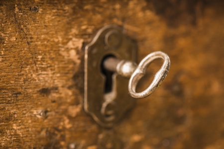 Old antique skeleton key in lock of wooden cabinet photo