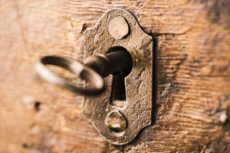 slot met sleuteltje: Oude antieke skeleton sleutel in het slot van de houten kast