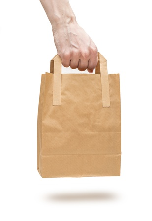 Closeup on white background of male hand holding brown paper bag with handles photo