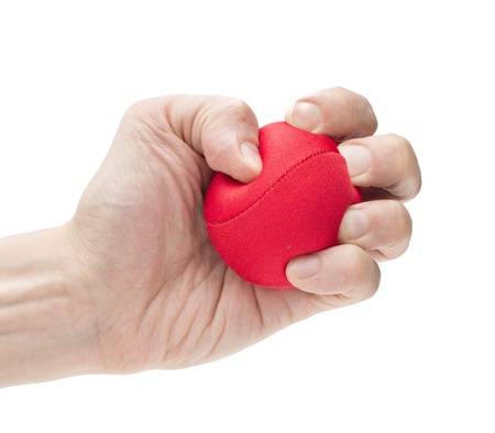 rubber ball: Closeup on white background of male hand with tight strong grip applying pressure on red ball