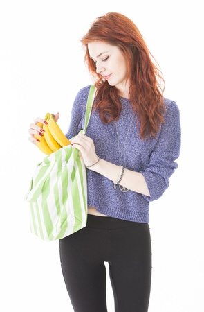 Cheerful young woman putting bananas in reusable eco friendly shopping bag