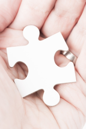 Closeup of a white puzzle piece in a human hand