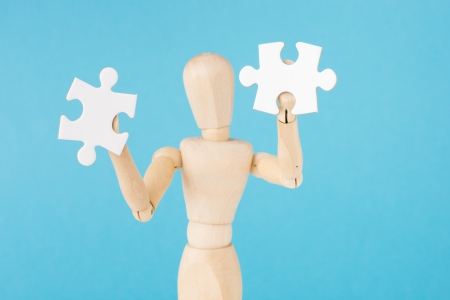 Conceptual image of creativity, teamwork and solutions. Wooden figurine holding two blank puzzle pieces. photo