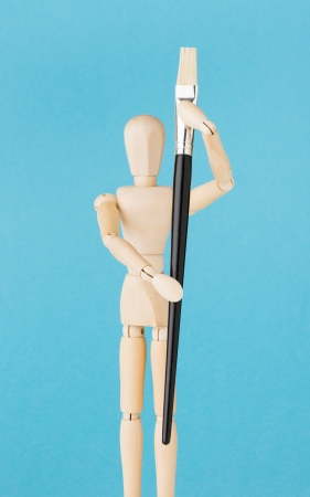 wood figurine: Imagen conceptual del arte y la pintura. Figurilla de madera sostienen pincel.