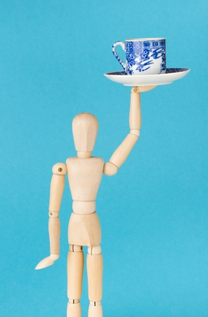 wood figurine: Imagen conceptual del trabajo en el caf�. Figurilla de madera camarera sirve una taza de caf�.