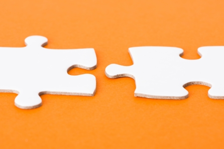 Close up of blank puzzle pieces on orange background photo