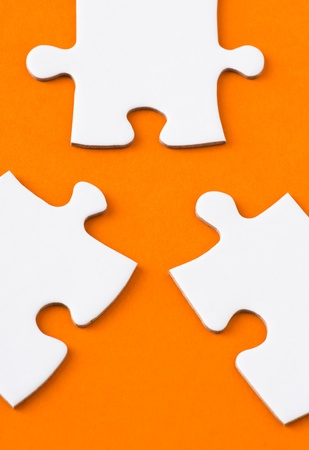 close fitting: Close up of two blank puzzle pieces in competition of fitting with a third