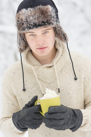 Christmas scene with natural looking teenage male outdoors in snow covered winter landscape.