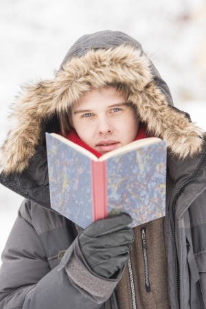 Christmas scene with natural looking teenage male outdoors holding a book.
