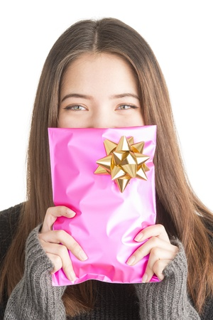 Natural beautiful teenage girl hiding behind christmas gift in pink wrapping and giggle