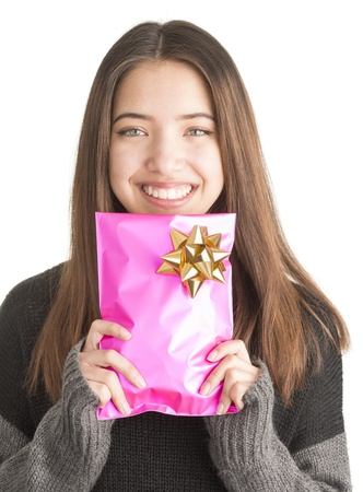 Happy beautiful teenage girl with christmas gift in pink wrapping Stock Photo