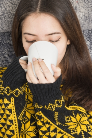 Beautiful teenage girl at breakfast with a white mug of steaming hot tea