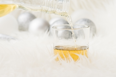 Glass of whiskey in festive holiday setting with christmas decorations as background