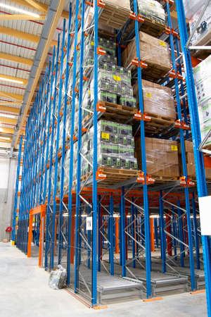 Interior view of a warehouse with racks, pallets, goods, forklifts