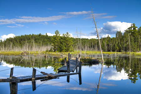 water scape: Broken wooden bridge on forest lake, reflection in water, Temagami, Ontario