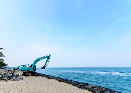 Excavator Machine with Raised Bucket on The Beach photo