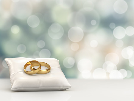 A pair of gold wedding rings on top of a pillow with bokeh background