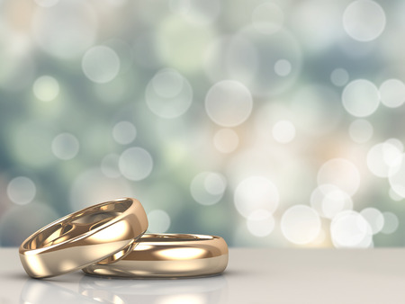 A pair of gold wedding rings with bokeh background