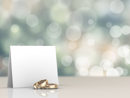 A pair of gold wedding rings and a card with bokeh background