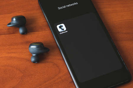 Kiev. 02.18.2021 - Clubhouse icon on a smartphone and headphones. Voice social network.