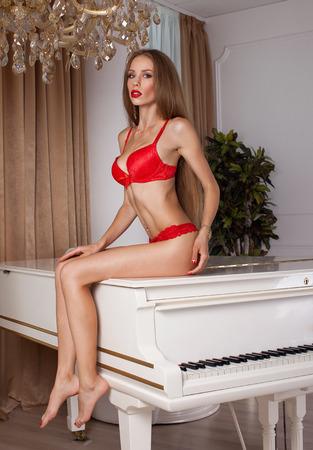 busty: Portrait of busty model posing in red lingerie. Studio shot. Red lips.