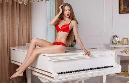 tetona: Retrato de modelo posando tetona en ropa interior roja. Estudio de disparo. Labios rojos.