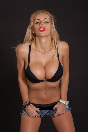 Fashionable blond beautiful woman posing in studio wearing short jeans, looking at camera. Big boobs. Red lips.