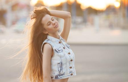 A portrait of a beautiful brunette young Caucasian woman outdoor. Young smiling woman outdoors portrait. Soft sunny colors.Close portrait.