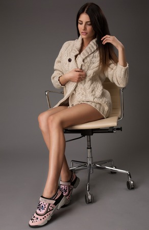 black stockings: Attractive sexy brunette female with bright sweater and black stockings posing smiling sitting on office chair. Portrait of sensual fair hair woman with long legs isolated on grey background