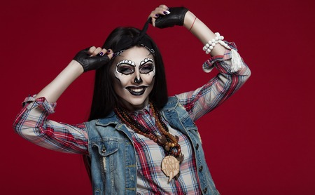 Closeup portrait of one beautiful wild young woman with bright golden animal makeup with thorns on face ion red background, horizontal picture. Halloween concept. Stock Photo