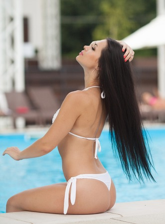 ombligo: Beautiful brunette girl in good shape with long dark hair and tan skin red lips in fashion swimming suite seating near the pool beach smile summer hot tan party. Sexy buttocks.