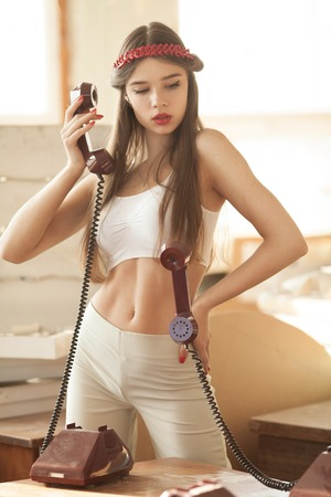 uneasy: pretty woman talking on old telephone. Fashion model. Red lips. Sunny color.