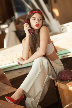 provoked: pretty woman talking on old telephone. Fashion model. Red lips. Sunny color.