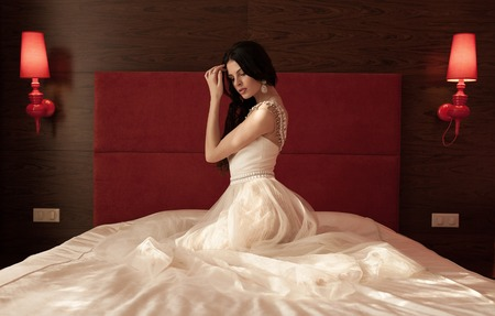 bridal salon: Hairstyle. Beautiful brunette bride girl with long healthy wavy hair styling and professional makeup in short lace wedding dress lying in white bed posing in modern interior. Stock Photo